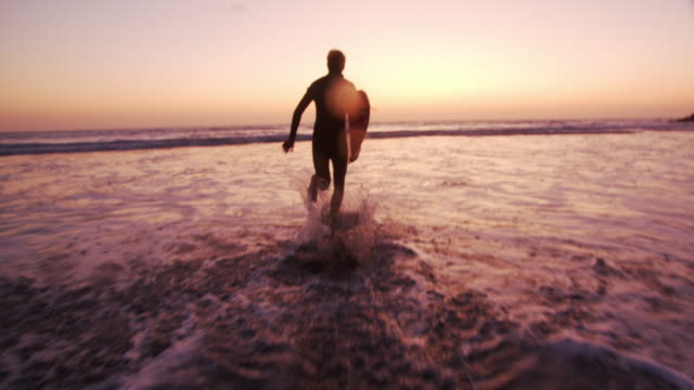 sm young man walking with his surfboard at sunset - brown hair stock videos & royalty-free footage