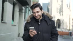 Young man walking with smartphone on city street in winter