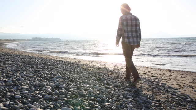 Young man walks along pebble beach, collecting firewood