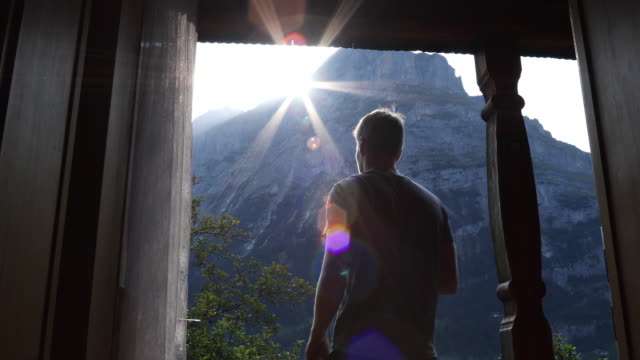 Young man walks onto chalet veranda, takes smart phone pic of mountains