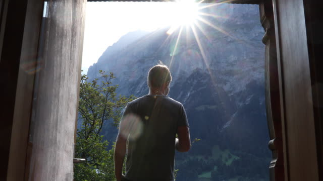 young man walks onto chalet veranda, takes smart phone pic of mountains - chalet video stock e b–roll