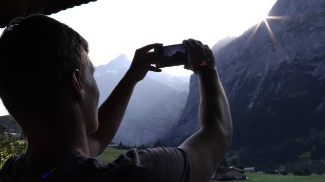 Young man walks onto chalet veranda, takes smart phone pic of mountains