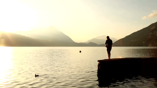 Young man walks out on pier to admire mountain lake at sunset
