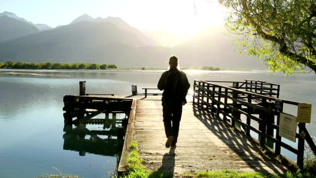 Young man walks out onto a dock at sunrise