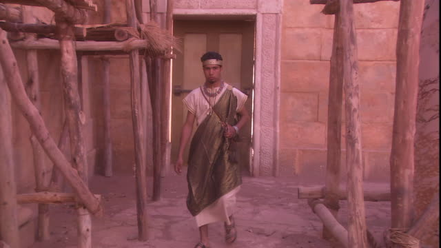 a young man walks through a temple construction site. - historische nachstellung stock-videos und b-roll-filmmaterial