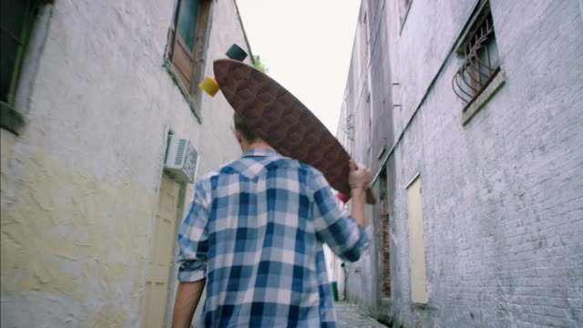 young man walks through downtown alley carrying custom wooden longboard - gasse stock-videos und b-roll-filmmaterial