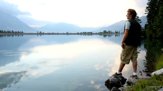 stockvideo's en b-roll-footage met young man walks to shoreline of mountain lake - steen rots