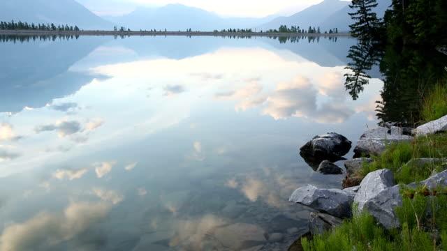 Young man walks to shoreline of mountain lake