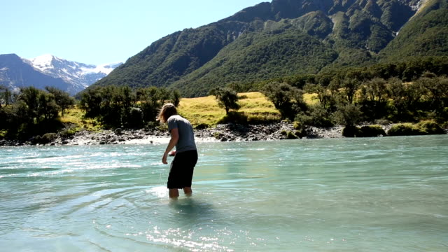 Young man walks upstream in shallow river water with glaciated mountains behind