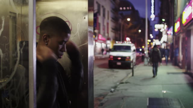 Young man wanders the streets of New York with phone booth