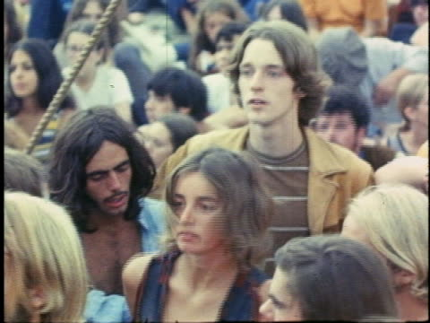 young man watches a young woman dance as other spectators focus on the music at the woodstock music festival. - 1969 stock videos & royalty-free footage