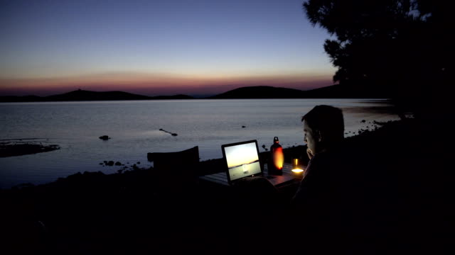 Young man watching video on his laptop next to the sea