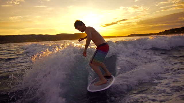 stockvideo's en b-roll-footage met young man wave surfing behind a boat at sunset - surfen