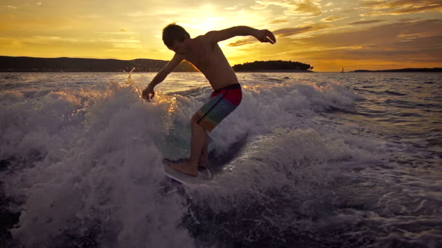 young man wave surfing behind a boat at sunset - skimboarding stock videos & royalty-free footage