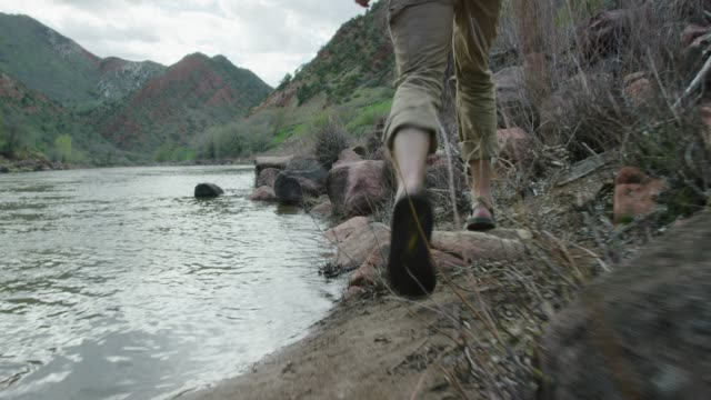 A Young Man Wearing a Backwards Baseball Cap and Sandals Hikes through Rocks at the Edge of the Colorado River in Colorado