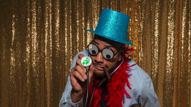 junger mann mit blauem glitzerhut und stethoskop beim posieren in der fotokabine - handsome people stock-videos und b-roll-filmmaterial