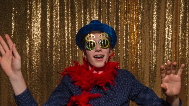 vidéos et rushes de jeune homme utilisant un chapeau et une écharpe bleus de scintillement et ayant l'amusement posant dans la cabine de photo - chemise