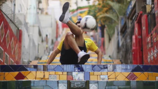 MS A young man wearing a Brazil t-shirt practices football skills on Selaron Steps (Escadaria Selaron) / Rio de Janeiro, Brazil