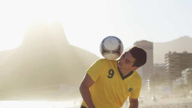 MS A young Man wearing a Brazil t-shirt practices Football tricks on Ipanema Beach / Rio de Janeiro, Brazil