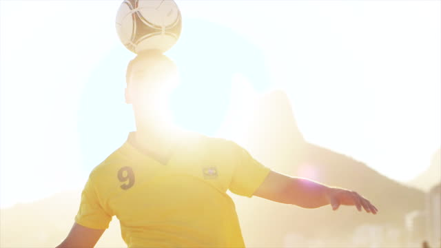 MS A young man wearing a Brazil t-shirt practices his football skills on Ipanema Beach / Rio de Janeiro, Brazil