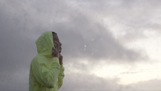 stockvideo's en b-roll-footage met young man wearing a hoodie in the rain - kleding