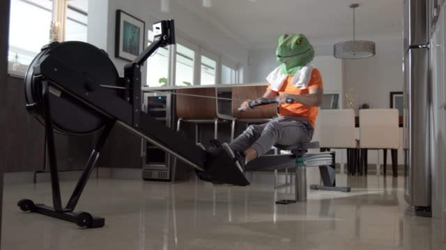 young man wearing a lizard mask during a rowing machine session - reptile stock videos & royalty-free footage