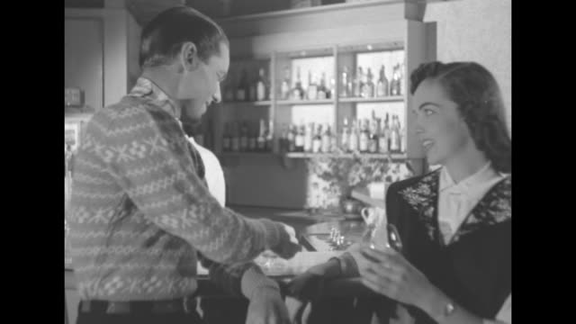 Young man wearing a patterned sweater and highwaisted pants stands at bar and hands his female companion a snifter of brandy and she drains it the...