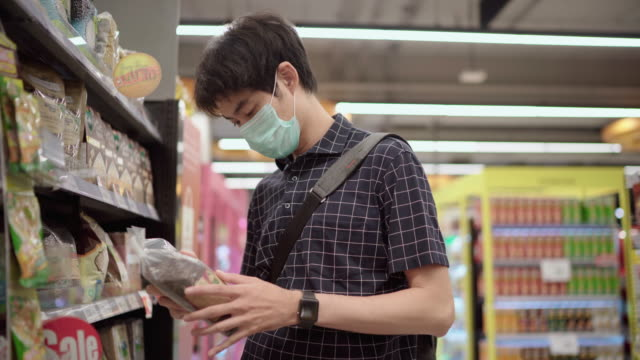young man wearing a protective face mask shopping in supermarket - prodotto per le pulizie video stock e b–roll
