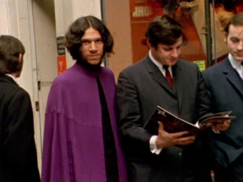 stockvideo's en b-roll-footage met a young man wearing a purple cape walks along carnaby street - kleding