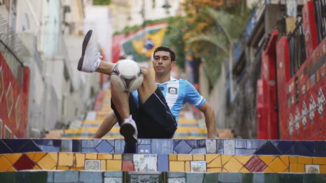 ms a young man wearing an argentina t-shirt practices football skills on selaron steps (escadaria selaron) / rio de janeiro, brazil - アルゼンチン文化点の映像素材/bロール