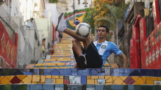 MS A young man wearing an Argentina t-shirt practices football skills on Selaron Steps (Escadaria Selaron) / Rio de Janeiro, Brazil