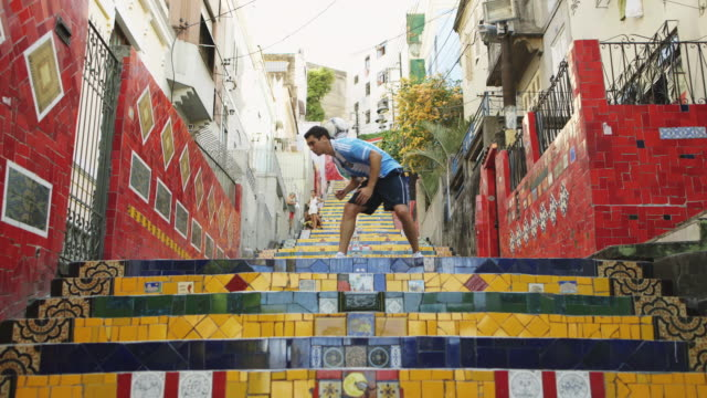 WS A young man wearing an Argentina t-shirt practices football skills on Selaron Steps (Escadaria Selaron) / Rio de Janeiro, Brazil