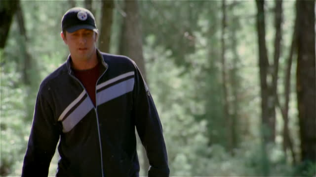 young man wearing baseball cap walking in the woods - baseball cap stock videos & royalty-free footage