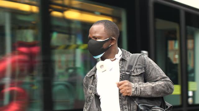 vídeos de stock, filmes e b-roll de jovem usando máscara facial dupla - ônibus