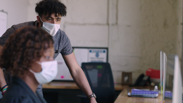 young man wearing face mask in office studies computer screen over coworker's shoulder at a distance - leaning stock videos & royalty-free footage