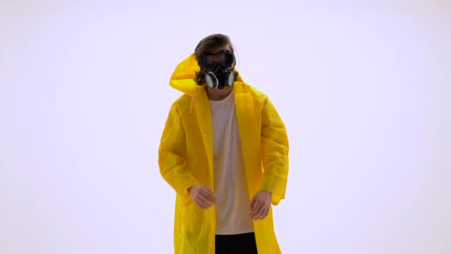 young man wearing raincoat and gas mask - gas mask stock videos & royalty-free footage