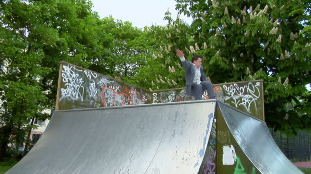 ws young man wearing suit inline skating on pipe, berlin, germany - 離れ技点の映像素材/bロール