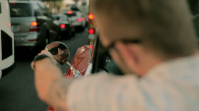 a young man wearing sunglasses adjusts the mirror on a vintage convertible as he waits in a long line of traffic. - teil einer serie stock-videos und b-roll-filmmaterial
