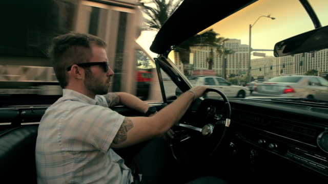 A young man wearing sunglasses drives a vintage, red convertible down a city street.