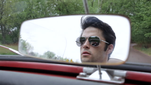 ms  young man wearing sunglasses driving convertible car in rural area visible through  rear view mirror / bayport, minnesota, united states - man convertible stock videos & royalty-free footage