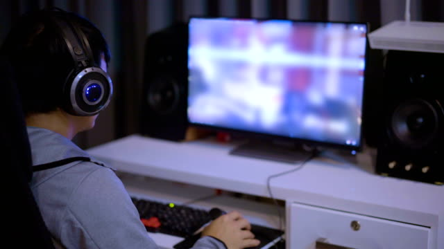 young man wears and gaming headsets and playing video games at home. - leisure games stock videos & royalty-free footage