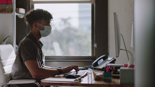 young man wears surgical face mask as he uses computer in office - office chair stock videos & royalty-free footage