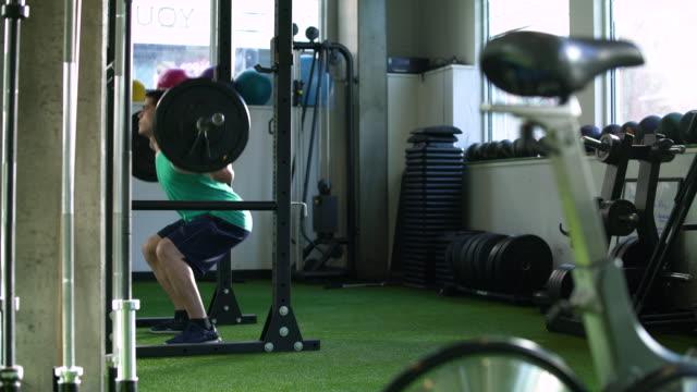 vidéos et rushes de young man weightlifting in a gym - seulement des jeunes hommes