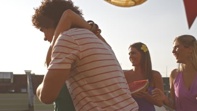 vidéos et rushes de jeune homme accueillants amies pour partie sur le toit - arrivée