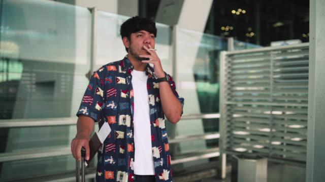 junger mann beim rauchen zigarette - zigarette stock-videos und b-roll-filmmaterial
