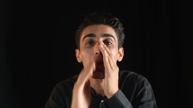 Young Man Whispering Gossip On Black Background