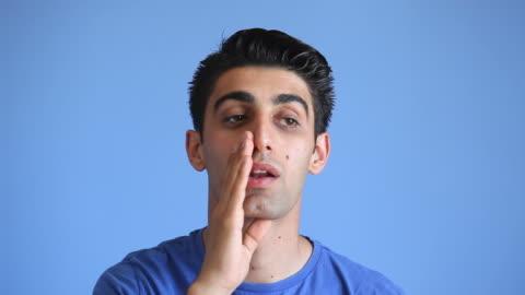 stockvideo's en b-roll-footage met jonge man whispering gossip op blauwe achtergrond - fluisteren