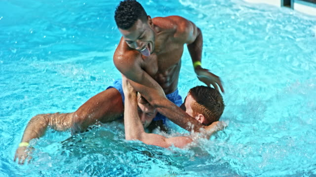 slo mo young man winning the shoulder wars with his friend in the pool at a pool party - shoulder ride woman stock videos & royalty-free footage