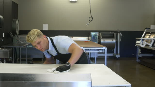 young man wiping a table in a butcher shop - lappen reinigungsgeräte stock-videos und b-roll-filmmaterial