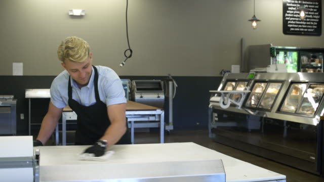 young man wiping a table in a butcher shop - washing up glove stock videos & royalty-free footage